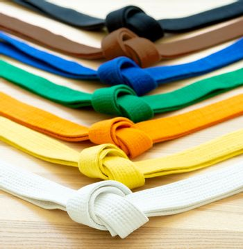 Martial arts colored belts on a wood background.