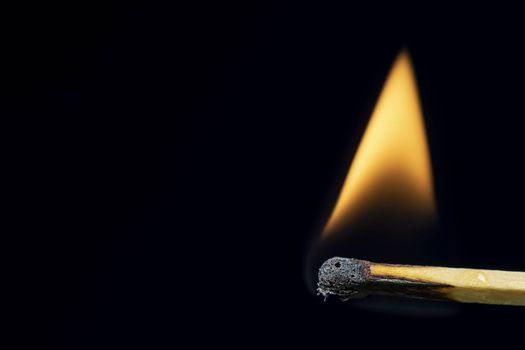 Match burning after being lit showing flame against black background with large copy space.