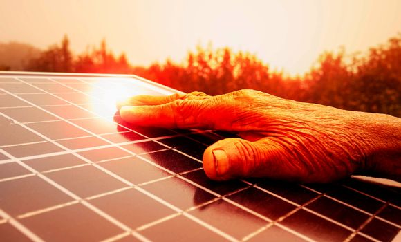 Close up of hand touching on solar panel outdoors.