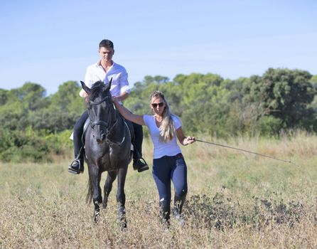 riding teenager are training her black horse with teacher