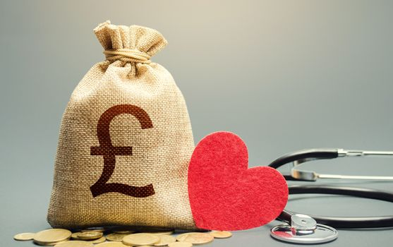 British pound sterling money bag and stethoscope. Health life insurance financing concept. Reforming and preparing for new challenges. Development, modernization. Subsidies. Funding healthcare system.