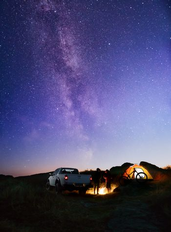 Two Male Friends near Bonfire, Pickup Offroad Truck, Illuminated Tent and Bike at Night Camp in the Mountains under the Night Sky with Milky Way. Bicycle Adventure and Car Travel Concept.