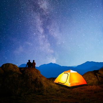 Young Couple Sitting Together on the Rock near Illuminated Hiking Tent and Enjoying the Beautiful Mountain View under Night Sky with Milky Way