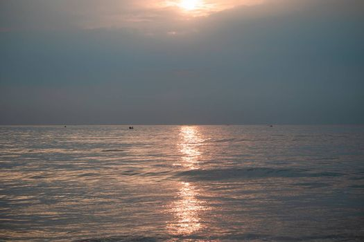 Sunrise in the morning from the clouds at Kovalam beach. and The sun's rays appear transparent in the sea water