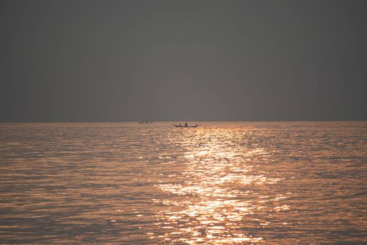 The sun's rays appear transparent in the sea water.Sunrise in the morning from the clouds at Kovalam beach in Chennai