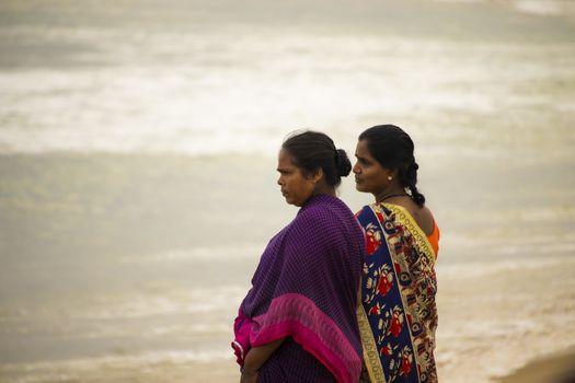 Chennai , Tamilnadu - India . September 2, 2020 . Two Tamil women watching the sunrise over Kovalam Beach