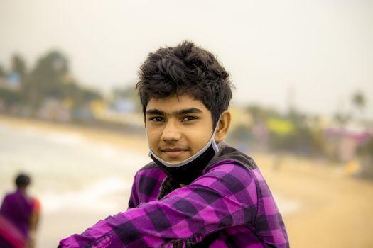 Chennai , Tamilnadu - India . September 2, 2020 .A Hindu boy enjoys Chennai beach in the morning with black face mask