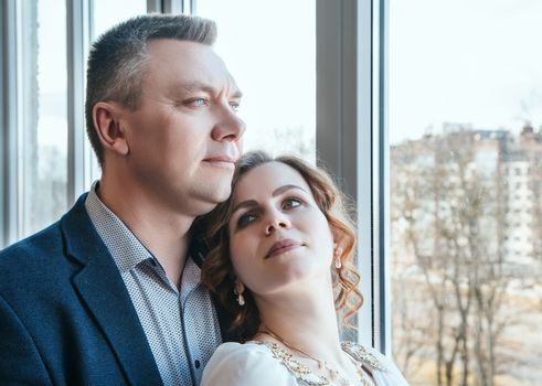 married couple standing by the window indoor in their home