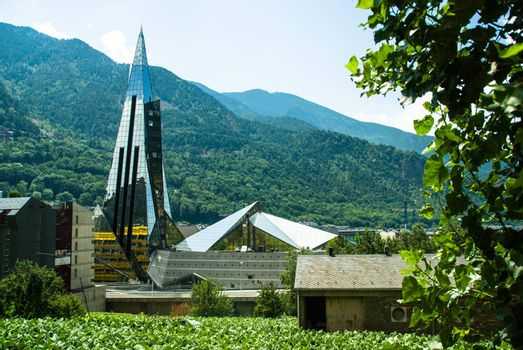 Caldea Spa glass building in Andorra with mountains at the background and tobacco fields at the foreground