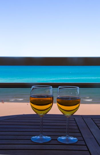 two glasses full of cider on top of a table with the sea in the background