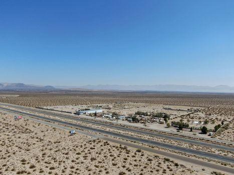 Aerial view of road in the middle of the desert under blue sky in California's Mojave desert, near Ridgecrest. Desert brush with road.
