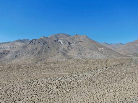 Aerial view of desert hills under blue sky in California's Mojave desert, near Ridgecrest. Small rock formations, desert brush.