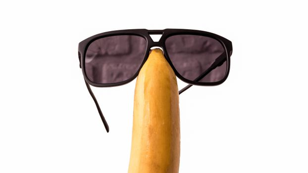 Sunglasses on a fruit head,isolated on white,funny banana with glasses,close-up.