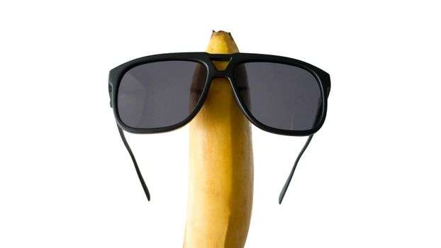 Banana in sunglasses isolated on white,close-up.
