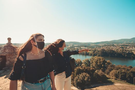 Two women look the panorama while one explains something, both using masks
