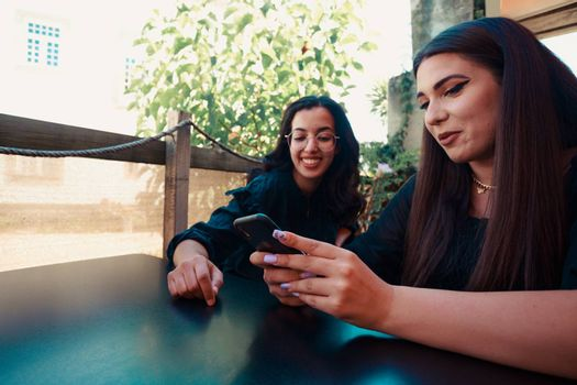 A woman showing something on the mobile phone to another women while they are impressed