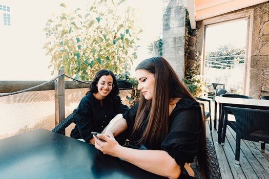 Young woman showing something on the phone making a friend laugh in the bar
