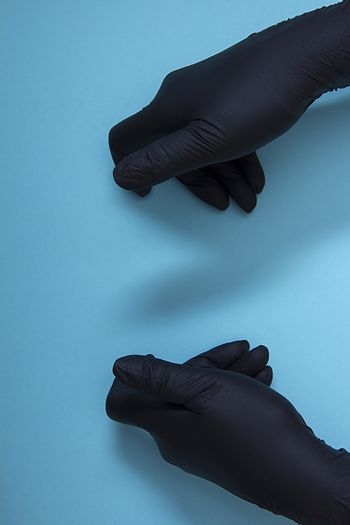 Hand holding or showing something in black nitrile protective gloves