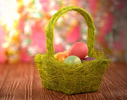 Basket with Easter eggs on a wooden background