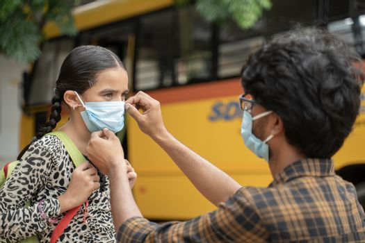 Father helping daughter to wear mask before getting inside the school bus as coronavirus or covid-19 safety measures - concept of back to school and new normal lifestyle.