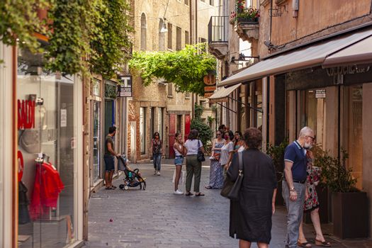 TREVISO, ITALY 13 AUGUST 2020: People walking in Treviso alley in Italy