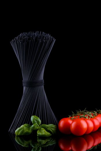 Black spaghetti with basel leaves and red tomato on black background.