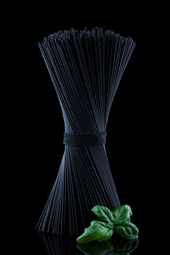 Black spaghetti with fresh green basel leaves with reflection on black background and place for text.