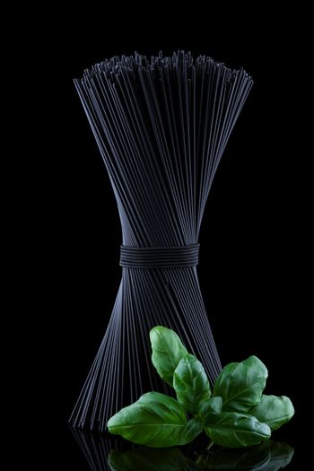 Black spaghetti with basel leaves on black background.