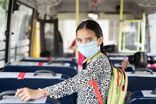 Portrait of Girl kid student in medical mask inside the school bus looking at camera - Concept of school reopen or back to school with new normal lifestyle.
