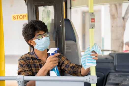 Young man in medical mask disinfecting or sanitizing bus by using alcohol Disinfectant spray to protect people from coronavirus or covid-19 infection