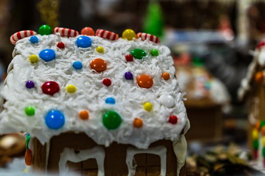 Colorful gingerbread house isolated on blurred background with Christmas decoration.