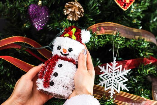 Hands holding Christmas snowman figurine in front of the Christmas tree. Decorating the fir tree isolated