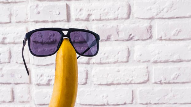 Banana in sunglasses on a brick wall background,close-up.