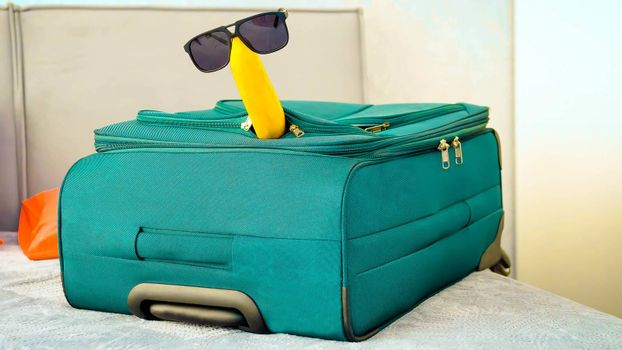 Banana in sunglasses with a suitcase in an apartment,in a hotel on the bed,close-up.