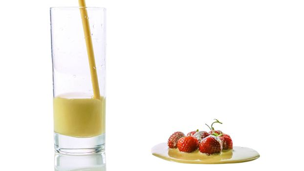 Pour yogurt into a glass close-up,fresh strawberry with yogurt isolated on white.