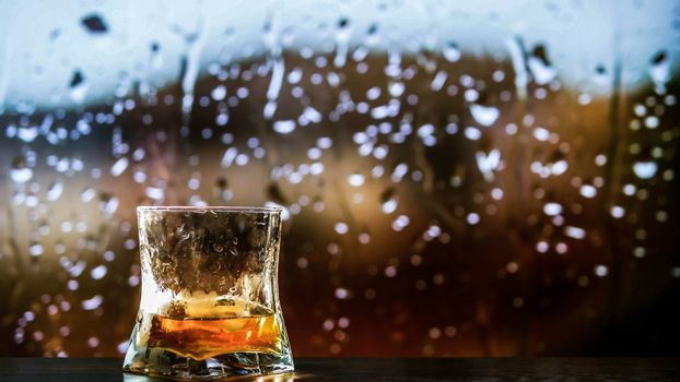 A glass of whiskey,brandy on the counter,an alcoholic drink in a glass of whiskey.Against the background of raindrops.
