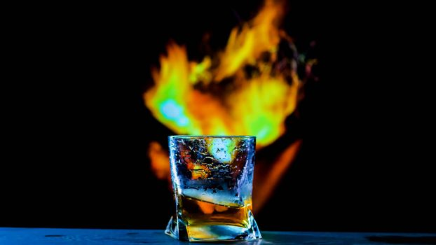 A glass of whiskey on a fiery background,an alcoholic drink on a bar counter,a cognac in a glass