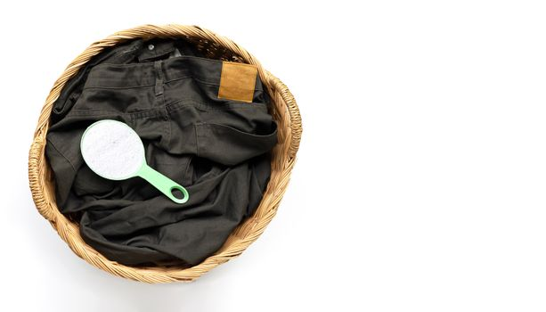 Trousers with measuring spoon of detergent powder in laundry bas