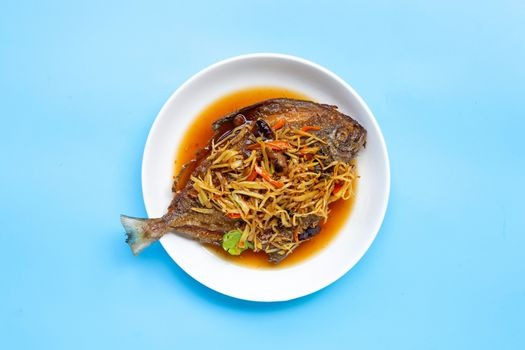 Deep fried fish with ginger and soy sauce on white dish plate on blue background. Top view