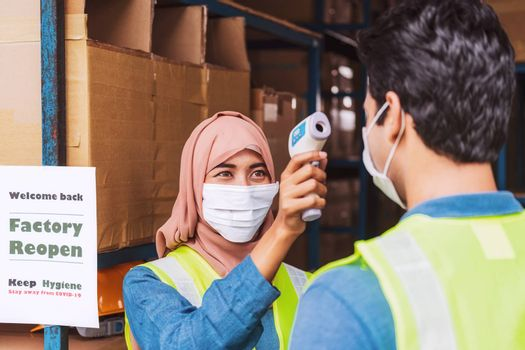 Muslim woman worker wearing surgical mask and Hijab uses Medical Digital Infrared Thermometer measure temperature to Indian man worker with safety clothes before start to work after warehouse reopen
