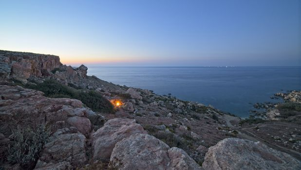 A campfire burns just after sunset at the rocky coastline of Selmun in Malta