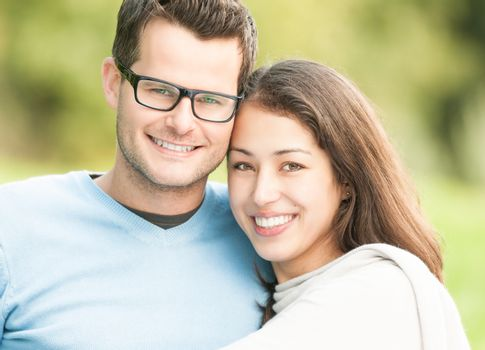 Portrait of beautiful romantic couple. People dating in park. Pretty woman with man in glasses and blue pullover. Green nature as background. Young positive family having leisure time outside.