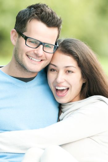 Portrait of young happy couple spending time together outdoor. Man and woman laughing and having fun. Love and romantic relationships. Harmony and happiness in family life.