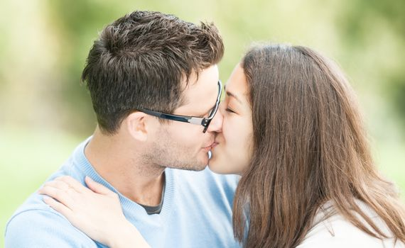 Handsome man in glasses and pretty woman kissing outdoors. Husband and wife giving kiss to each other in park. Happy family expressing feelings. Portrait of beautiful romantic couple in love.