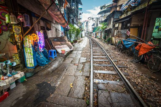 Perspective view of railway running along narrow street with houses in Hanoi, Vietnam. Unusual solution of transport problem. Dangerous neighborhood for people. Travelling and tourism.