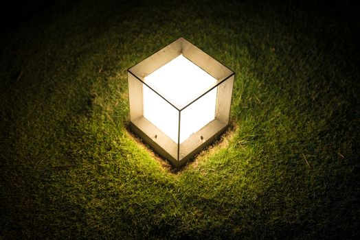 Garden lantern in shape of cube with dim light striking upon green lawn at night. Outdoor decoration and lighting. Warm and romantic atmosphere of evening. Illumination in garden or park.
