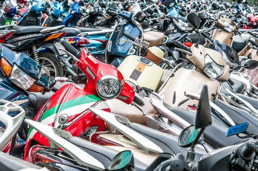 Great number of different motorbikes on parking zone. Rows of colorful scooters. Cheap and fast way of travelling in city. Popular means of transport, especially in Asian countries.