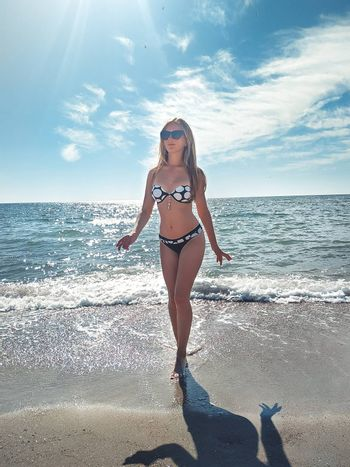 Beautiful young girl walking smiling resting relaxing on the white sand tropical beach near sea with perfect slim sport body in bikini