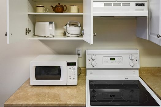 Open cabinets and primary appliances on average home kitchen.