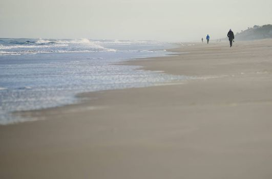 Incidental people walking along the beach of Atlantic Ocean. USA